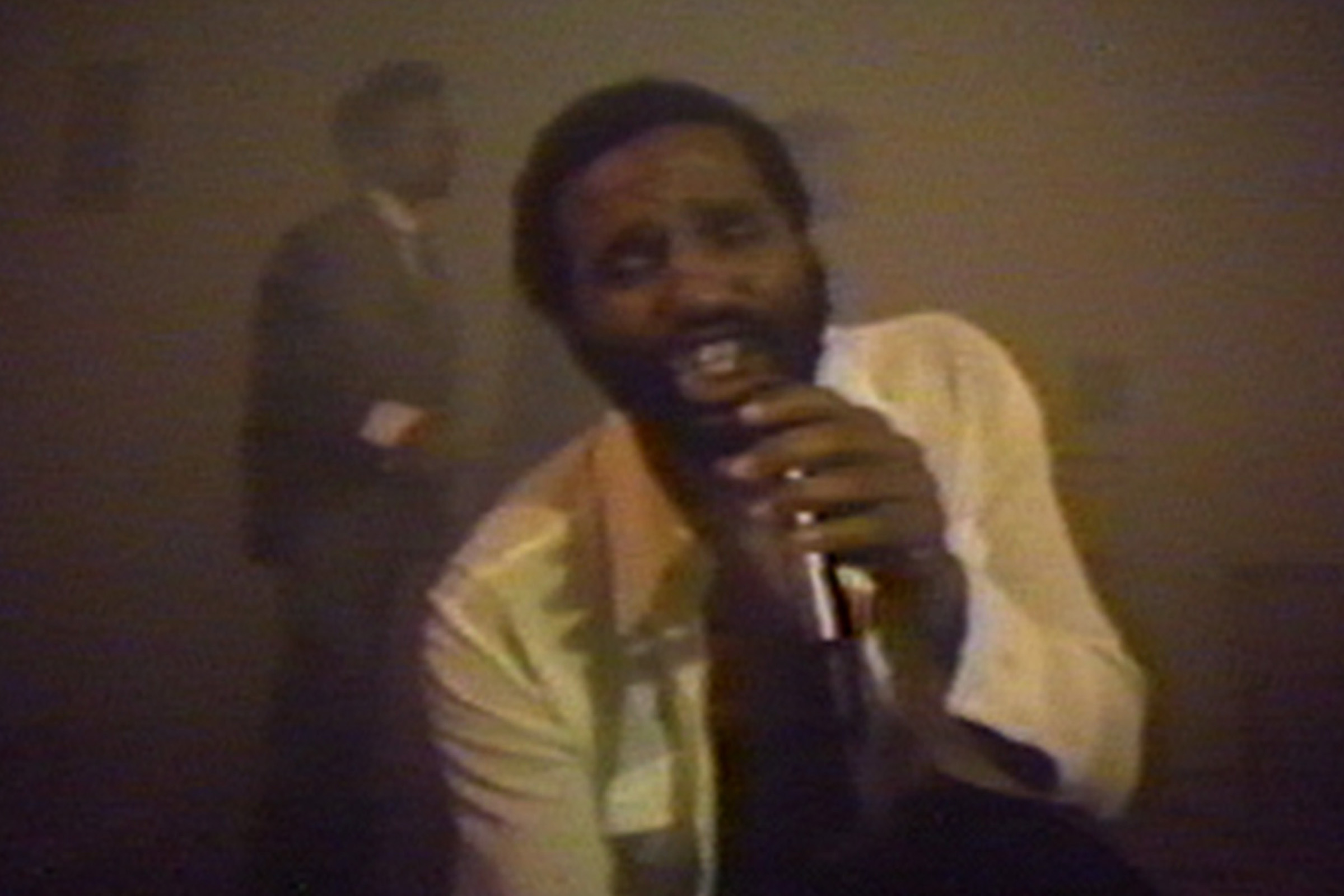 Video still from Two-Zone Transfer, showing Ulysses Jenkins singing into a handheld microphone.